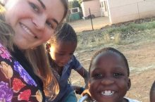 Carolyn Moe takes a selfie with children in Botswana.