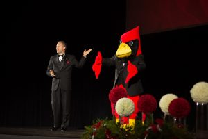 Vice President of University Advancement, Pat Vickerman, on stage with Reggie Redbird.