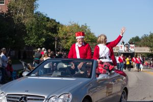 two people waving from car in parade