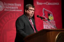Larry Dietz at a wood podium with banners for Illinois State University in the background.