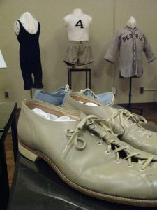 Bowling shoes from the 1930s with outfits on mannequins in the background