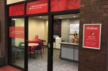 The open, glass doors of the Printing Services Office, with a red banner and a desk.