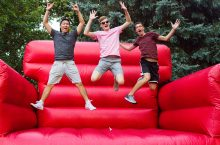 Illinois State students jump on inflatable red chair on the quad