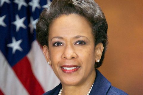 Former U.S. Attorney General Loretta E. Lynch standing in front of an American flag.