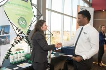 employers graciously greets a Redbird candidate at a career fair