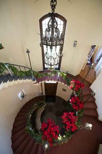 winding stairwell covered in garland and poinsettias