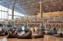 Tiered rows of stacks of books set against a vaulted ceiling of concrete and glass. People in large bean bangs in the foreground.