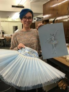 Photo of Amanda Vander Byl, posing with her completed tutu and original rendering.