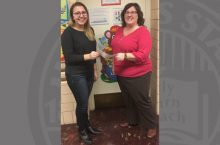 NSSLHA representative Melissa Jenkins receives a check from CSD staff member Tricia Larkin.