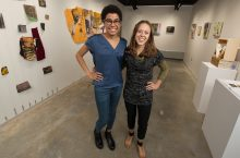 Whitney Johnson and Alissa Palmer pose in the gallering featuring their work.
