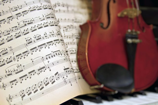 Music Sheets and Notes with Blur Violin on Piano Background