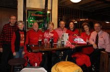 Group of people in red smiling at table