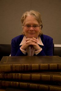 Historian Lynn Hunt with her head propped on her folded hands behind a stack of books