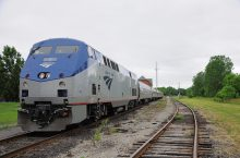 Amtrak train driving across a track in a rural area.