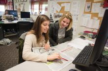 Two students working on a page layout for the Vidette student newspaper.