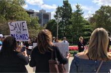 crowd gathered on the University Quad with signs and media coverage