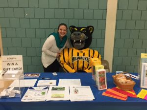 Lauren with mascot at health fair table