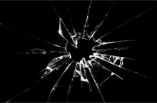 image of glass shattered by a bullet hole