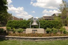 Large bell surrounded by flowers and set in stone landscaping, with academic buildings in the background