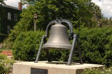 Large bell surrounded by flowers and set in stone landscaping, with trees in the background