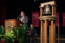 President Larry Dietz at a podium with the replica of the Founders Bell beside him.
