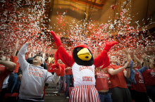 reggie mascot with arms up as confetti falls