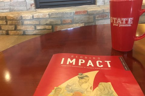 Redbird Impact magazine on table next to coffee mug and in front of fireplace
