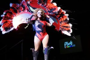 Drag performer with plumed costume on stage.