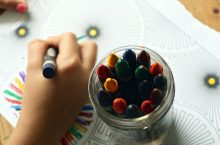 ECE student coloring with crayons