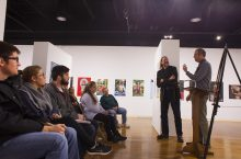Two men stand a podium and address an audience seated in an art gallery.