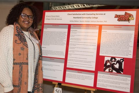woman standing in front of a poster of her research on counseling services