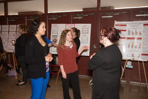 Three people discussing the work at the at the University Research Symposium