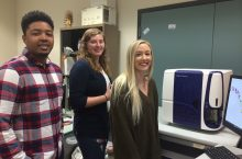 Three students standing in front of the new machine