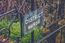 VIntage Style Photo Of A District Nurse Sign On A Garden Gate