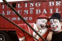 Two clowns in front of a baggage wagon