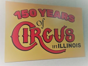 "Yellow sign with red lettering that states ""150 years of Circus in Illinois"""