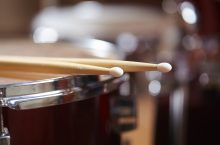 Drums conceptual image with close up of drum rim and drum sticks