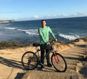 Cirstin next to a bike on the beach