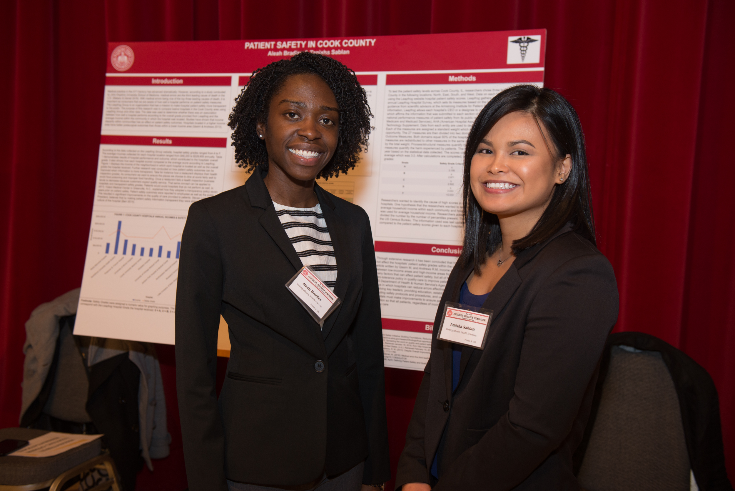 Aleah Bradley and Tanisha Sablan in front of poster