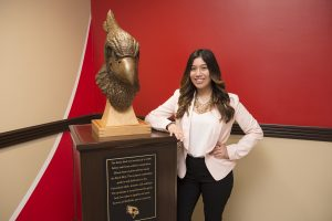 Sarah Aguilar standing by the Reggie bust in Hovey Hall.