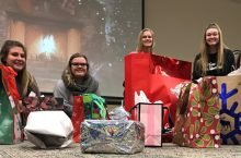 Four girls smile behind presents