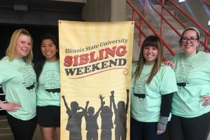 Four women smile in front of Sibling Weekend sign
