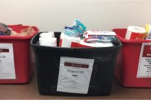 Three bins filled with toothbrushes, paper towels, soap and other items for teenagers in temporary housing.