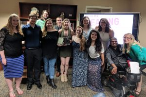 9 students, 2 authors, and instructor pose for picture.
