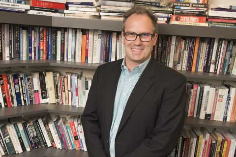 Andrew Hartman standing in front of shelves of books