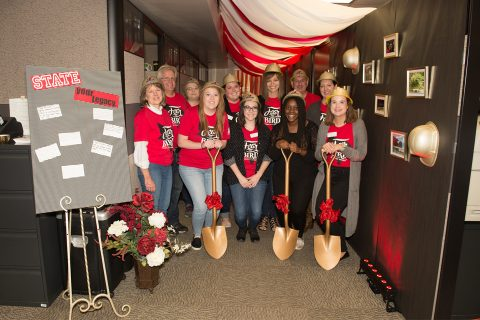 group of people in hallway holding shovels
