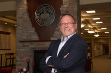 Ed Manley smiling in Alumni Center, in front of the ISU seal
