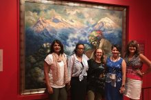Five women standing in front of a painting
