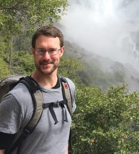 Man with a backpack standing in front of mist-covered foliage