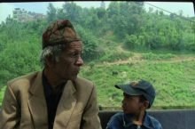 older man and a young boy in a tram in Nepal